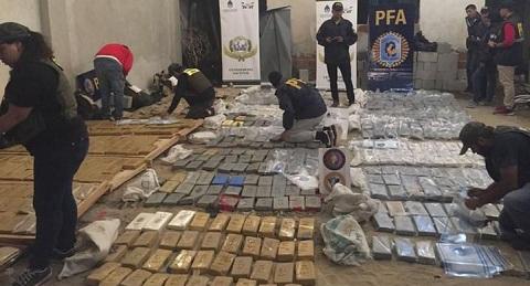 Los policías federales acomodan los paquetes que tenían el logo de un ave rapaz. Télam